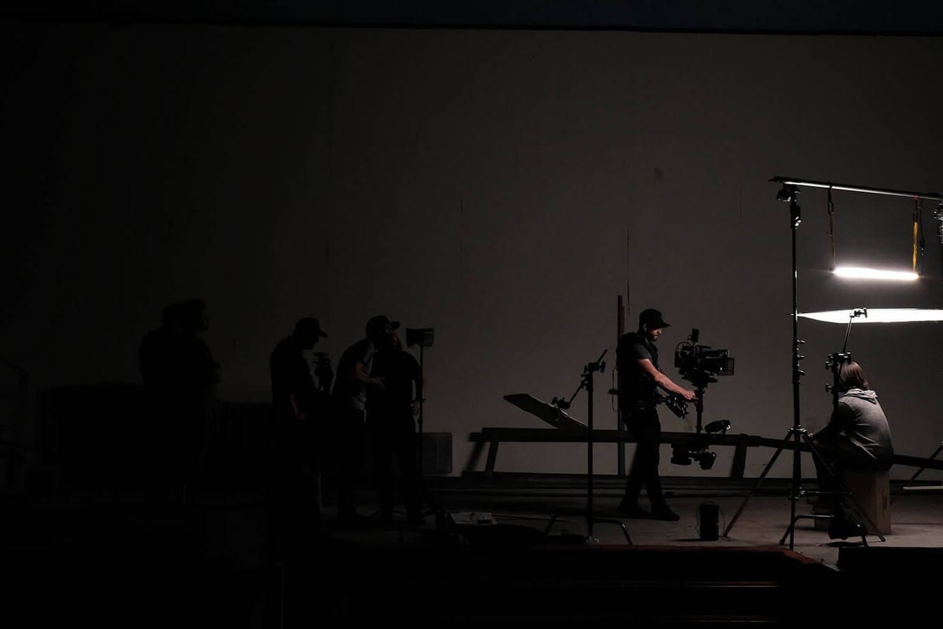 image of filmmakers with lights, cameras and microphones in darkly lit room, preparing to shoot a scene