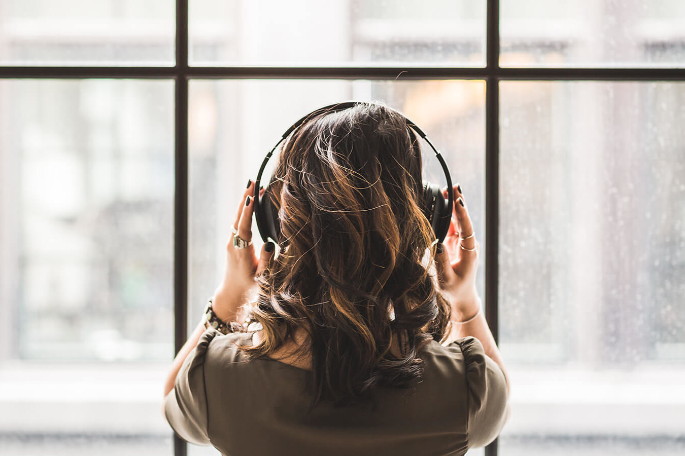 image of young woman wearing headphones, listening, looking out the window, womens audio mission