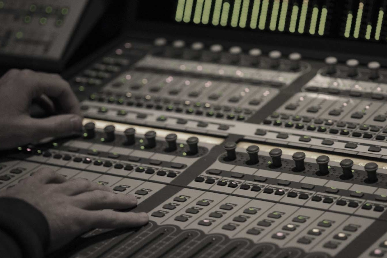 image of a sound engineer's hands on the faders of a mixing console