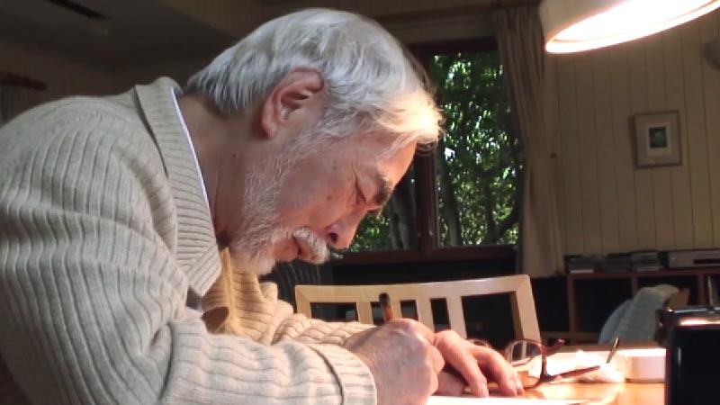 photo of hayao miyazaki sketching away