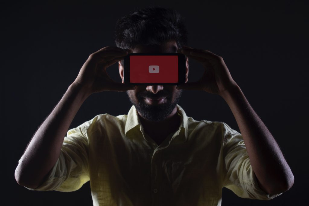 A Man with Android Smartfonem that has youtube app turned on
