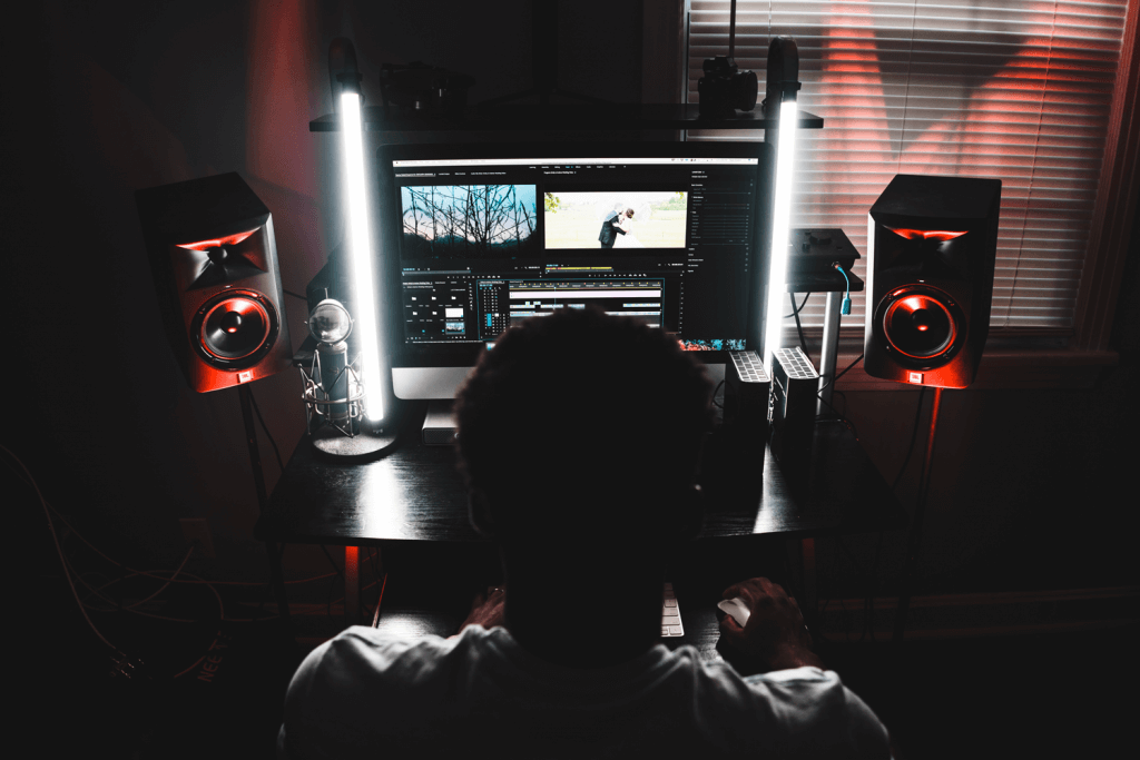 man in front of a PC, editing in premiere pro