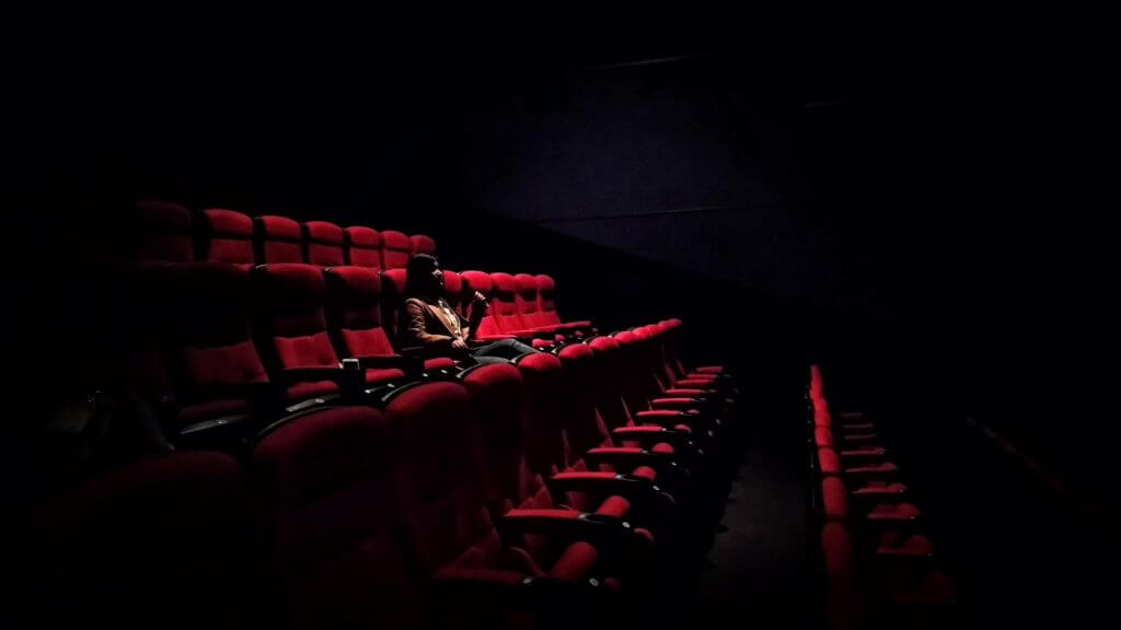 person sitting in an empty cinema